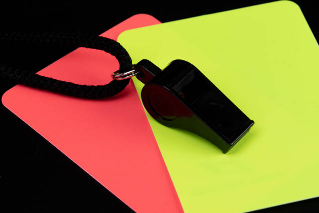 Referee cards with referee whistle on black background