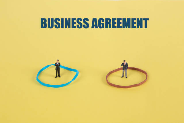 Two businessman standing in cirles and Business Agreement text on yellow backgound