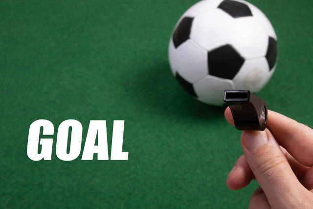 Sports whistle, soccer ball and Goal text on green grass
