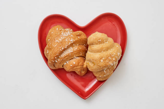 Two croissants on the heart-shaped plate