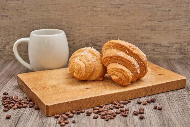 Coffee cup and raw coffee beans with tasty croissants on the wooden cutting board
