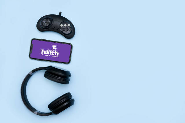 Game controller, wireless headset and mobile phone with Twitch logo on the display