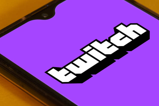 Twitch app launch screen with logo on the display of a black mobile smartphone