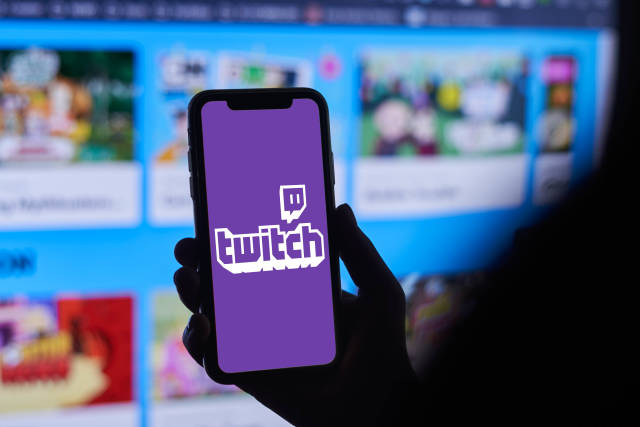 A person holding iPhone app Twitch providing streaming game and video live streaming