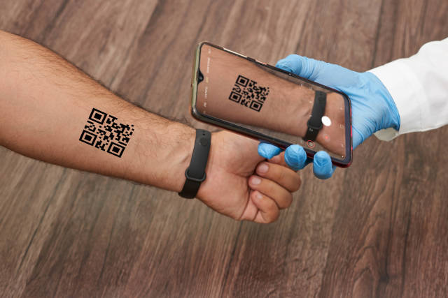 A doctor checking COVID vaccination QR code