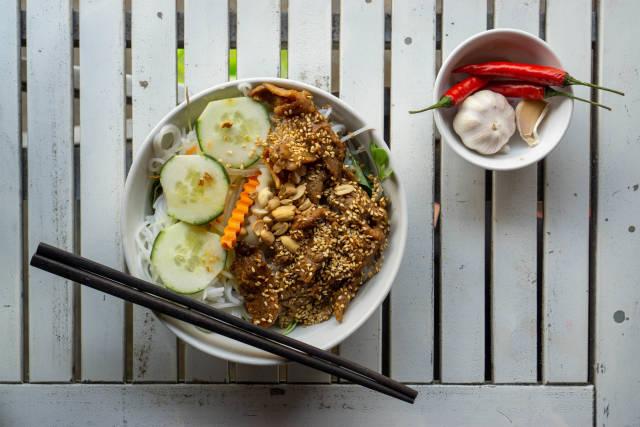Vietnamesisches Gericht Bun Thit Nuong mit Reisnudeln, gegrilltem Schweinefleisch, Sesam, Gurken, eingelegten Karotten und Ernüsssen von oben auf einem weißen Holztisch fotografiert