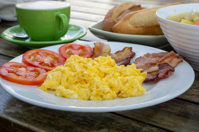 Close Up Food Photo of Breakfast with Scrambled Eggs, Bacon Strips, Tomatoes, Baguette, Cappuccino and Fruit Bowl on a Wooden Table