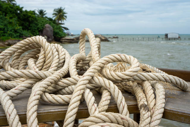 Close Up Photo of Nautical Ropes on a Wooden Bar Table with Ocean and Tropical Forest in the Background