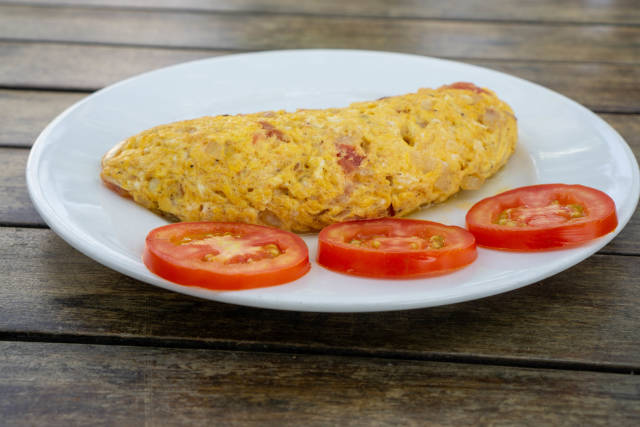 Close Up Food Photo of Egg Omelette with Onions and Bacon on a White Plate with Tomato Slices on a Wooden Table