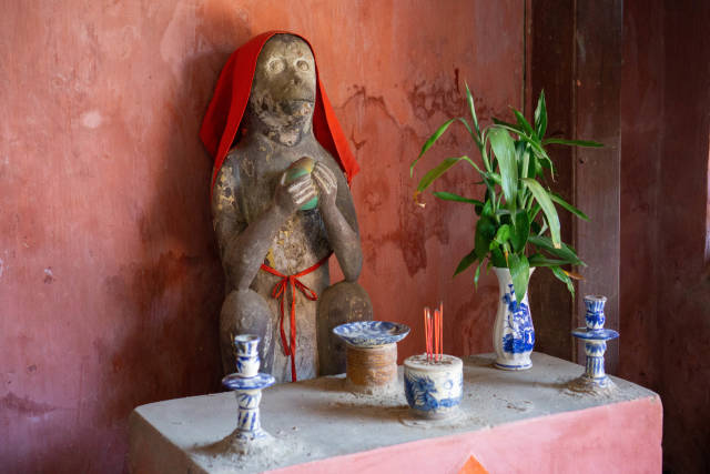 Altar with Flowers and Incence Sticks in front of a Monkey Stone Statue on one End of the Japanese Covered Bridge in the Old Town of Hoi An, Vietnam