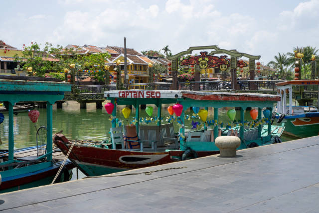 Wooden Tourist Boats with Colorful Lanterns with Bridge of Light in the Background in the Ancient Town of Hoi An, Vietnam