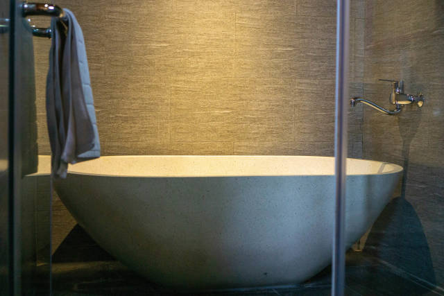 Chrome Faucet over a Large Stone Bathtub in a Hotel Bathroom with Shower Towel hanging on a Glass Door