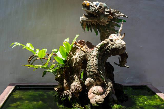 Drachen Statue mit Pflanzen in einem kleinen Teich in der Phuc Kien Pagode in Hoi An, Vietnam