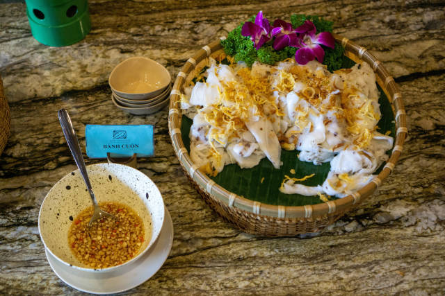 Top View Food Photo of Vietnamese Rice Rolls Banh Cuon with Fried Onions next to a Bowl of Fish Sauce with Garlic and Spices at a Breakfast Buffet at a Hotel in Vietnam