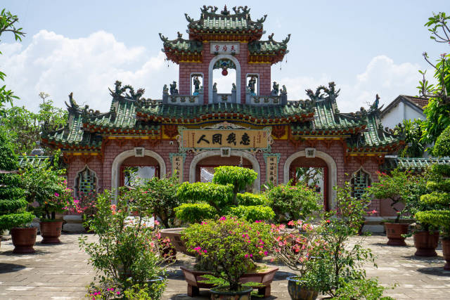 Courtyard with many different Plants and Trees in front of a Stone Entrance Gate with large Chinese Letters, Ornaments and Statues at the Phuc Kien Pagoda in Hoi An, Vietnam