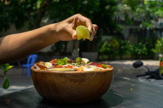 Person squeezes a Lime over a Healthy Salad Bowl with Basil, Boiled Quail Eggs, Honey Mustard Sauce and Chicken in a Garden of a Restaurant