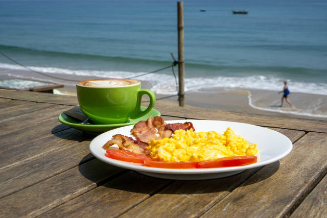 Cup of Cappuccino and Scrambled Eggs with Tomatoes and Bacon Strips for Breakfast in the Sun at An Bang Beach in Hoi An, Vietnam