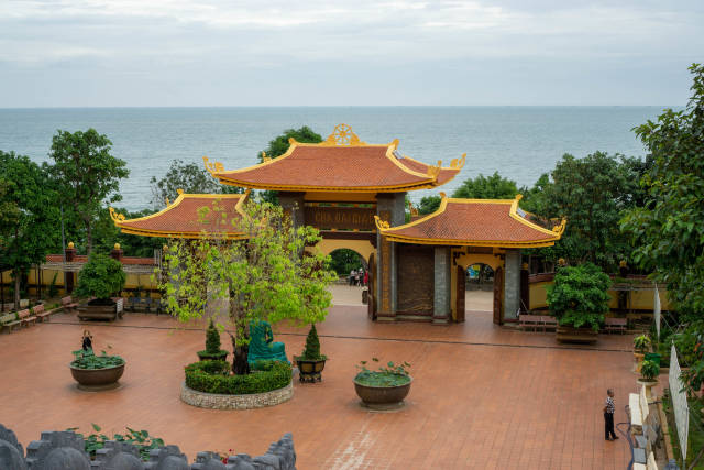 Entrance Gate, Large Courtyard, Trees, Plants and Buddhist Statues with a View to the Ocean at Ho Quoc Temple in Phu Quoc, Vietnam