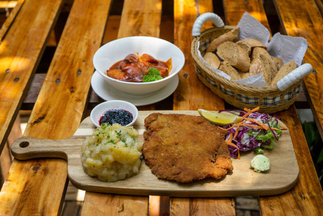 Food Photo of Chicken Schnitzel with Potato Salad on a Wooden Board, Currywurst in a Ceramic Bowl and a Basket of Bread Slices on a Wooden Table in a German Restaurant