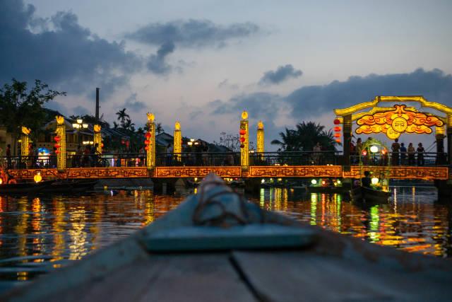 Nacht Foto von der Brücke der Lichter mit Touristen auf Booten mit beleuchteten Laternen und Reflektionen im Thu Bon Fluss in Hoi An, Vietnam