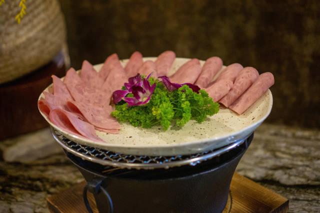Schinkenwurst Aufschnitt mit Petersilie und Dekoration auf einem Teller bei einem Hotel Frühstücksbuffet Nahaufnahme
