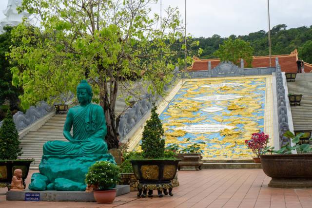 Buddha Statue mit Bäumen und Pflanzen vor einer großen goldenen Drachen Verzierung am Ho Quoc Tempel in Phu Quoc, Vietnam