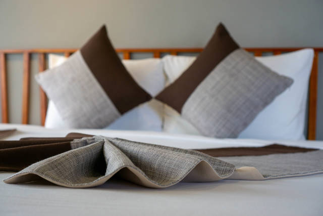 Close Up Photo of Creative Folded Bed Runner on a Large King Size Bed in a Hotel Room
