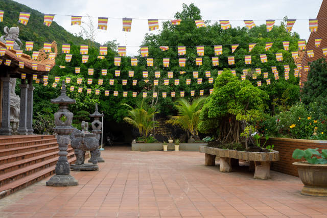 Buddhist Flags between two Pagoda Buildings in the Temple Complex of the Truc Lam Ho Quoc Zen Monastery in Phu Quoc, Vietnam