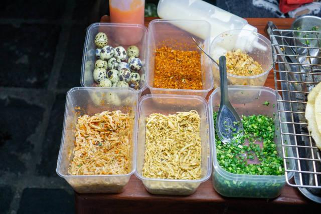 Plastikschalen mit Zutaten wie Wachteileier, Chili, Frühlingszwiebeln und Shrimps für Vietnamesische Pizza Banh Trang Nuong bei einer Straßenküche in Hoi An, Vietnam