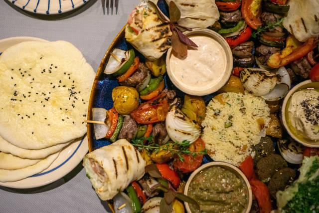 Orientalische Sultan Platte mit vielen verschiedenen Gerichten wie Hähnchen Shawama, Hummus, Falafel, Pita Brot, Gegrilltes Gemüse, Rindfleisch Spieße und Soßen von oben fotografiert