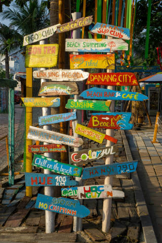 Colorful Wooden Signboards with City Names, Sights and Holiday related Words at the Entrance of a Beach Bar in Da Nang, Vietnam