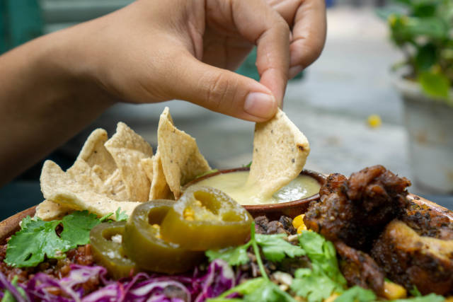 Close Up Food Photo of Person dipping a Tortilla Chip in Honey Mustard Sauce with a Mixed Salad Bowl with Grilled Chicken, Jalapenos, Cabbage and Herbs in the Foreground
