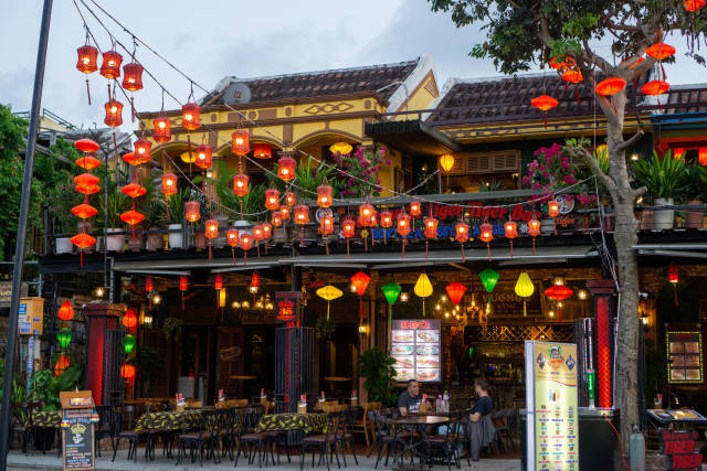 Open Restaurant with many Plants, Lanterns in different Shapes and Colors and Outdoor Seating in the Pedestrian Street in Hoi An, Vietnam