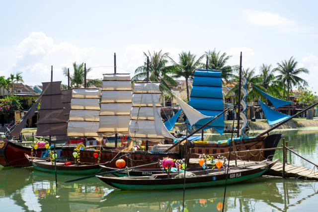 Small Wooden Sailing Boats with Colorful Lanterns for Tourists on a River with Palm Trees in the Background in the Old Town of Hoi An, Vietnam