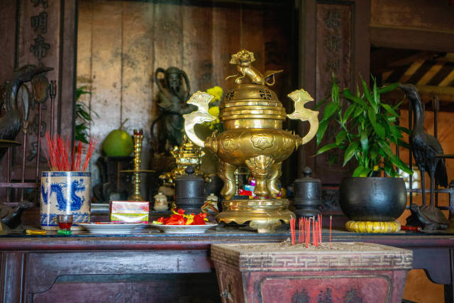 Wooden Altar with Small Statues, Incense Sticks, Offerings and Golden Items inside the Japanese Covered Bridge in Hoi An, Vietnam