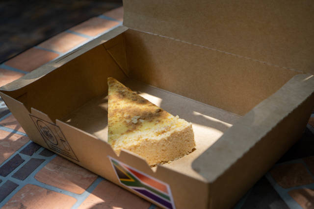 Close Up Food Photo of a Slice of Cheesecake in an Environment-Friendly Take-Away Paper Box on a Garden Table in the Sun