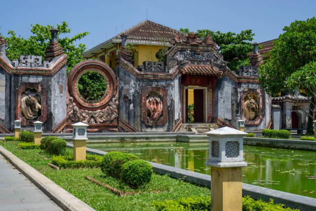 Historisches Ba Mu Tempel Tor mit großem Teich bei blauem Himmel in der Altstadt von Hoi An, Vietnam