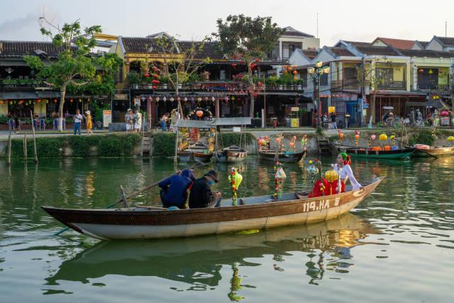 Touristen auf einem Ruderboot mit bunten Laternen auf dem Thu Bon Fluss mit Restaurants und Shops im Hintergrund in der Altstadt von Hoi An, Vietnam