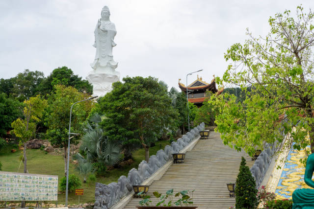 Large Lady Buddha Statue at the Buddhist Temple Truc Lam Ho Quoc with many Trees and Plants on Phu Quoc Island in Vietnam