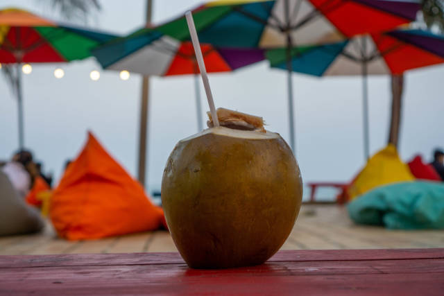 Close Up Photo of Fresh Coconut with Drinking Straw on a Wooden Table with Sun Umbrellas and Bean Bags of a Beach Bar in the Background