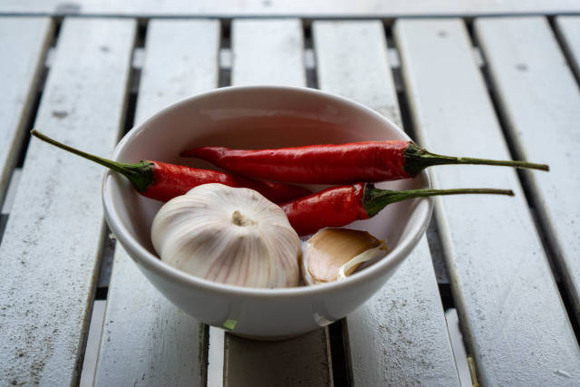 Close Up Photo of Fresh Thai Red Chilis in a Small Ceramic Bowl with Garlic Cloves and a Garlic Bulb on a White Wooden Table