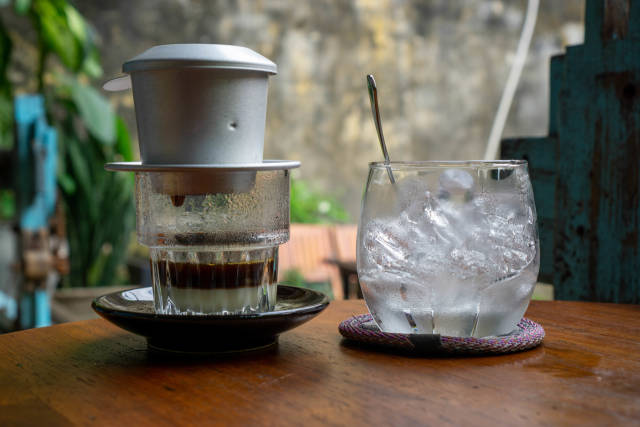Traditional Vietnamese Drip Coffee with Condensed Milk in a Glas next to a Glas of Ice Cubes at a Cafe in Hoi An, Vietnam