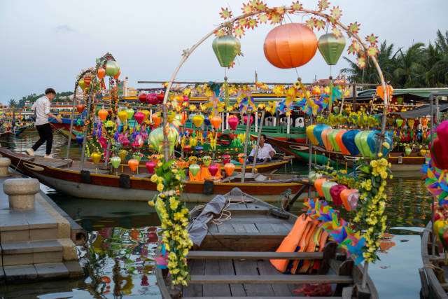 Colorful Lanterns and Flowers attached to Wooden Rowing Boats for Tourists to take a Boat Ride in the Ancient Town of Hoi An, Vietnam