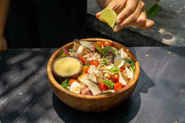 Person drückt eine Limette über einem gesundem Salat mit Hähnchenbrust, Parmesan, Kirschtomaten, Basilikum, Geröstetem Brot und Honig Senf Sauce aus