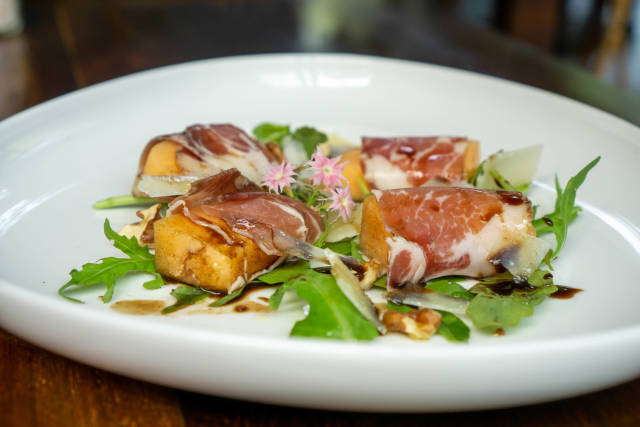 Close Up Food Photo of Honeydew Melon wrapped in Parma Ham with Arugula, Parmesan Cheese and Balsamic Dressing on a White Plate