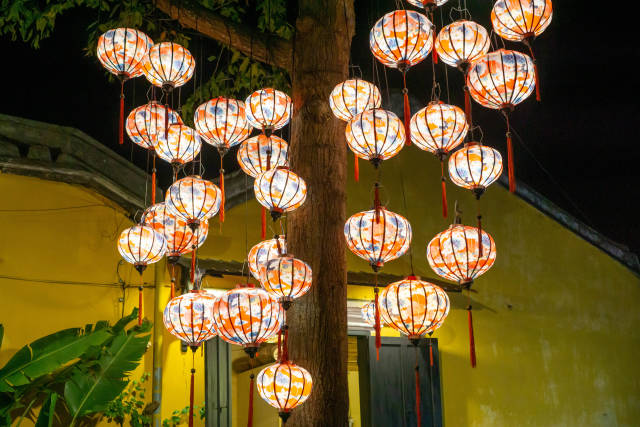Colorful Handmade Lanterns with Light Bulbs hanging on a Tree in front of a Yellow Building in Hoi An, Vietnam