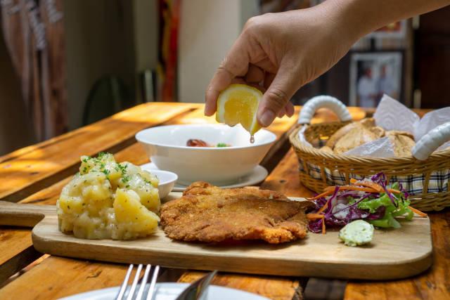 Person drückt eine Zitrone über einem Hähnchen Schnitzel aus auf einem Holzbrett mit Kartoffelsalat, Beilagensalat und Kräuterbutter in einem deutschen Restaurant