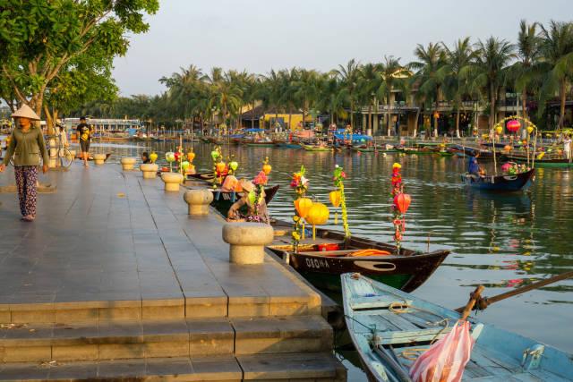 Bäume und Palmen entlang der Promenade am Flussufer vom Thu Bon Fluss mit vielen Ruderbooten dekoriert mit bunten Laternen für Touristen in Hoi An, Vietnam