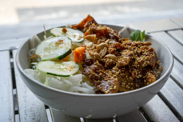 Close Up Food Photo of a Bowl of Vietnamese Bun Thit Nuong with Rice Vermicelli, Grilled Pork Meat, Sesame, Cucumber, Pickles and Peanuts on a White Wooden Table