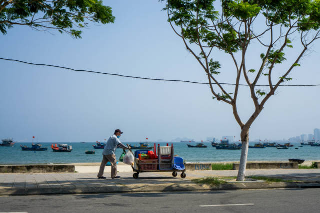 Man pushing a Street Food Cart with Plastic Chairs and Tables on a Sidewalk with Fishing Boats in the East Vietnam Sea in the Background in Da Nang, Vietnam